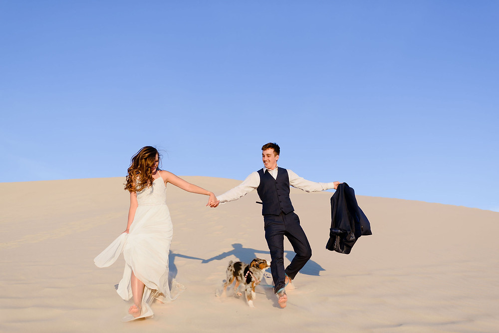 couple holds hands and runs down the sand hill towards the camera. they are smiling really big and are dishelved from bounding
