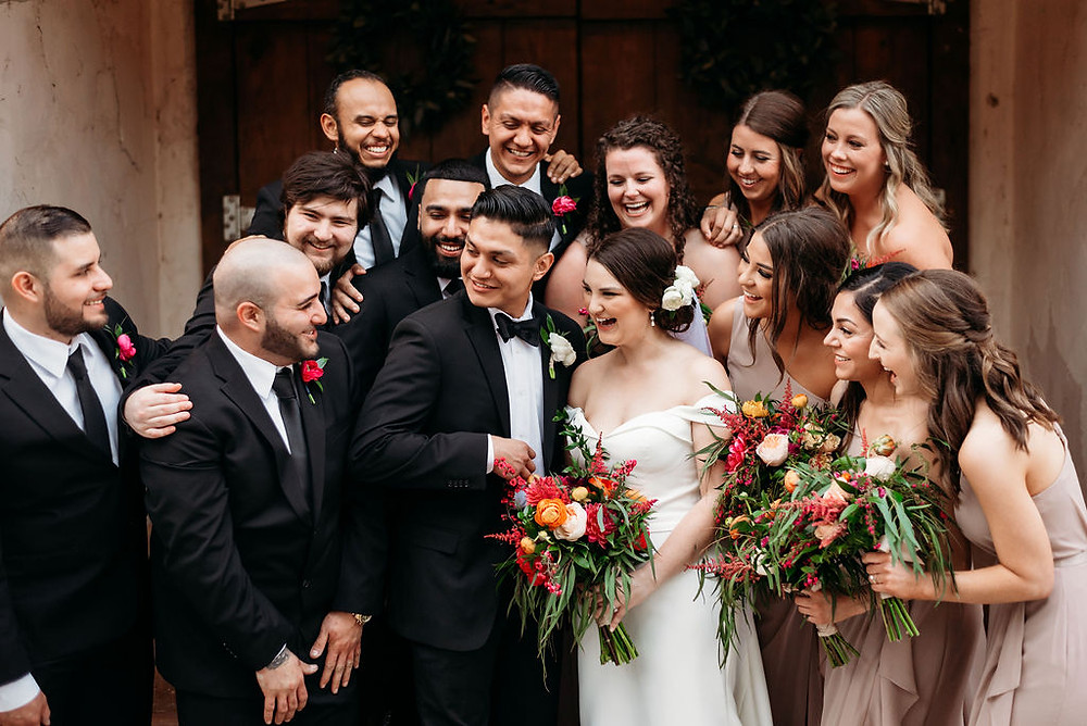 candid laughing wedding party photo on steps of chapel at villa antonia