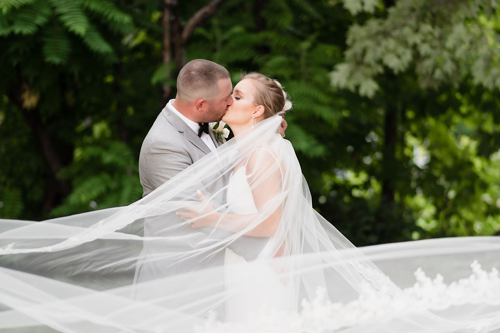 bride and groom kiss while the veil swoops in front of the camera