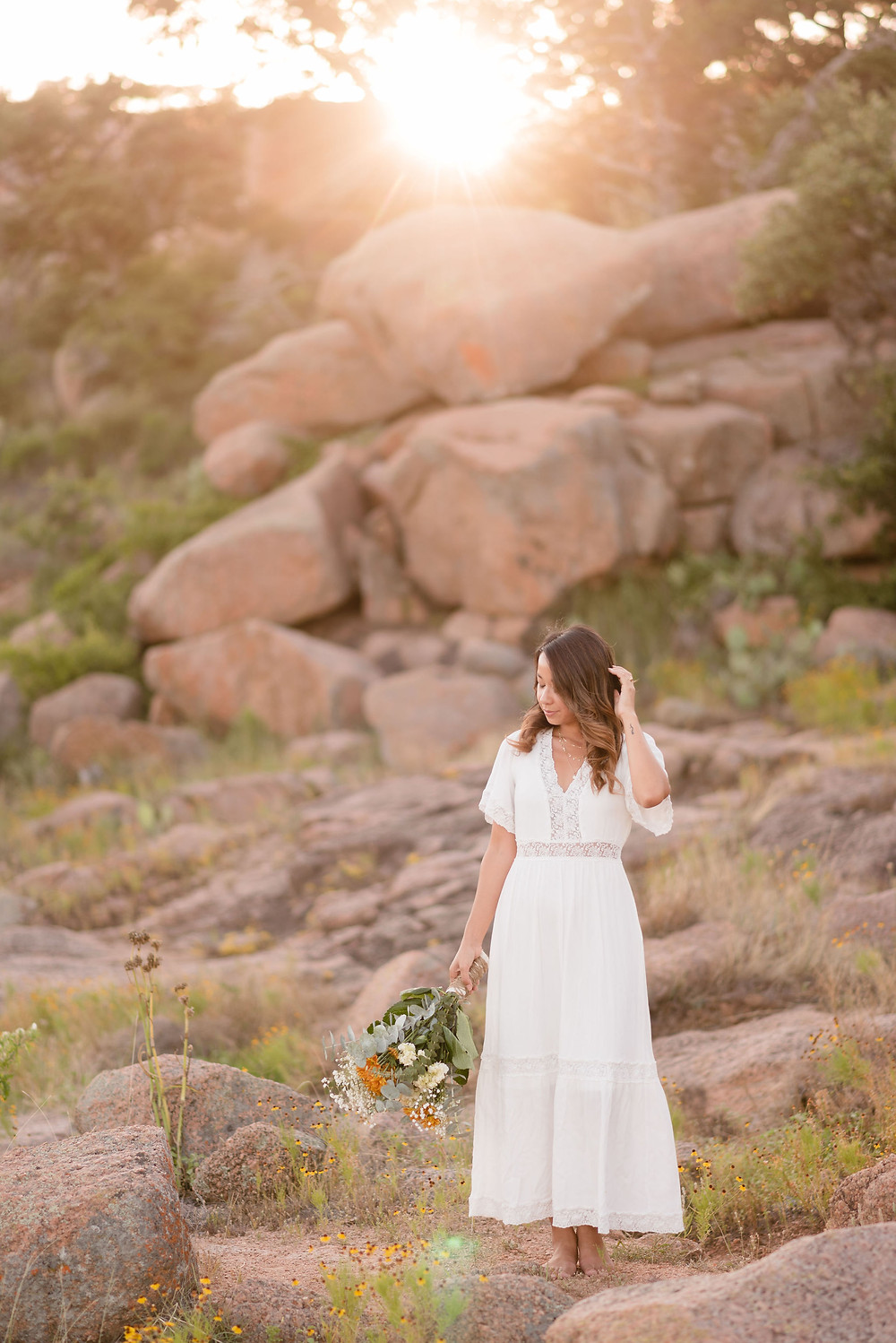 bride standing barefoot on rocks with the sun beaming behind her
