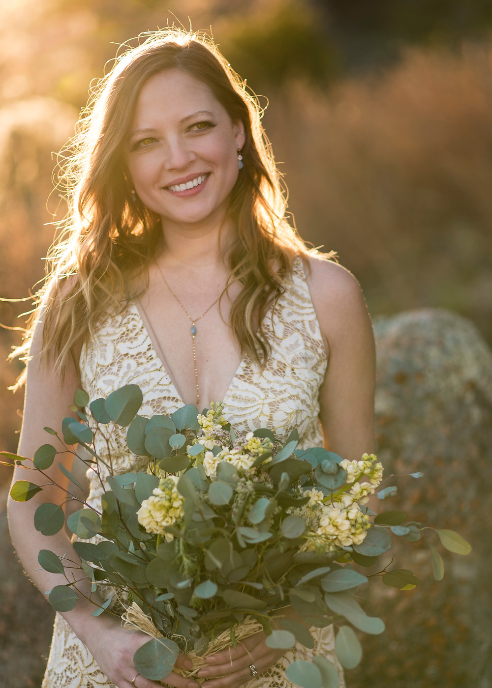 bride smiling holding bouquet of greenery and white flowers. The sun is setting behind her giving her hair a beautiful back lit halo. Bride is at enchanted rock for her elopement