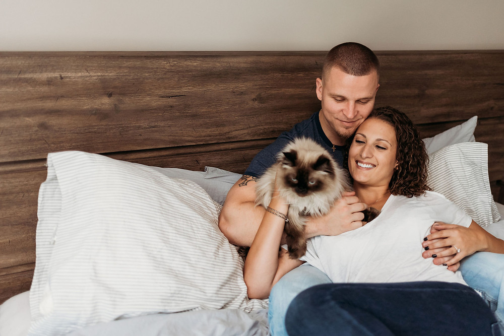 a couple with their cat in bed during their in home engagement session