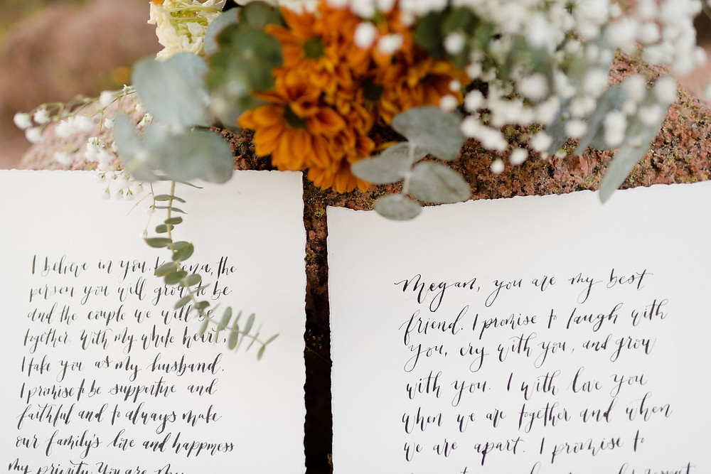 paper with handwritten vows and a bouquet of flowers