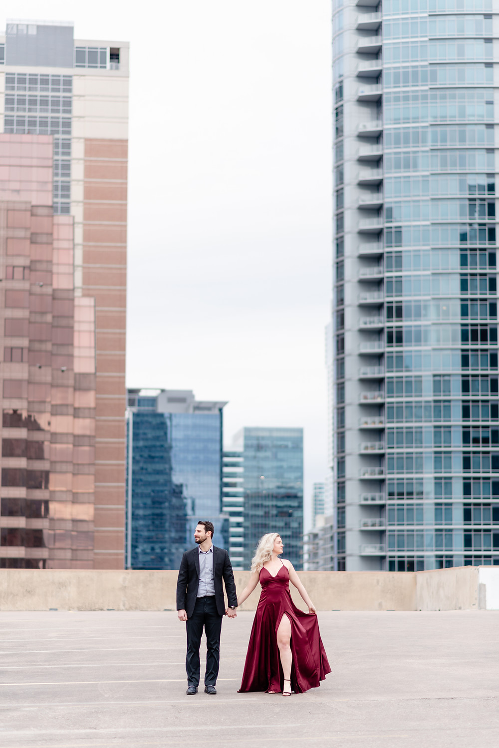 couple in formal attire stands on a rooftop in downtown Austin Texas for engagement session