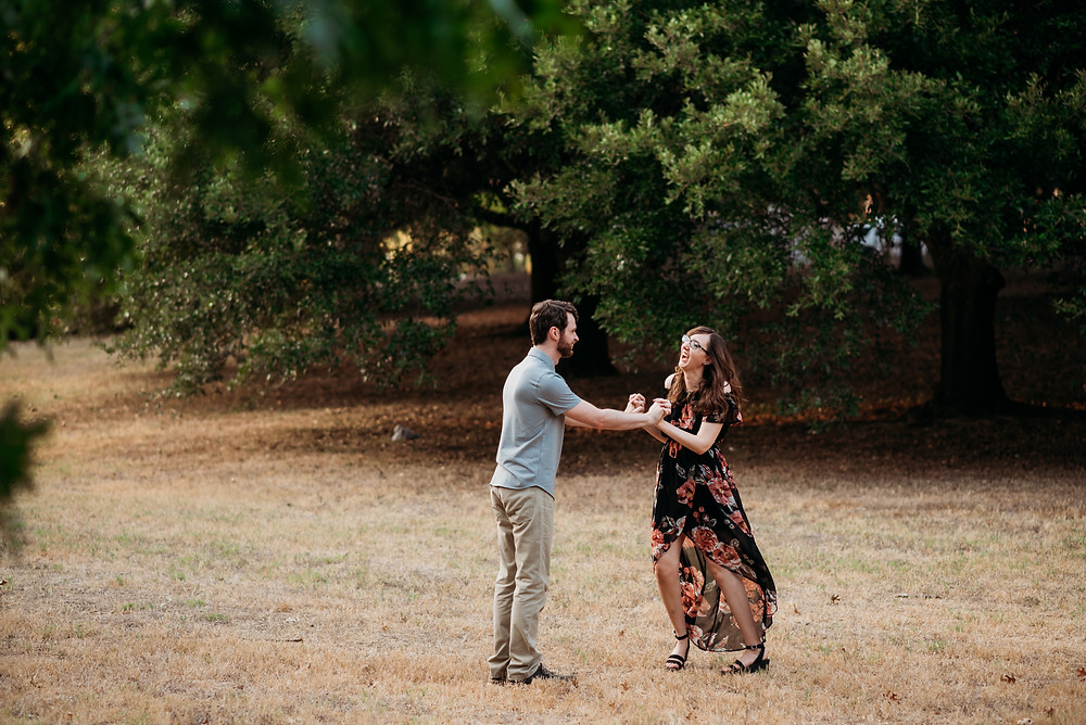 girl and guy are facing each other and holding hands. their arms are extended so they are not standing close to each other. the girl is laughing and her dress is blowing in the wind. they're playing a game/prompt to keep their engagement photos lively