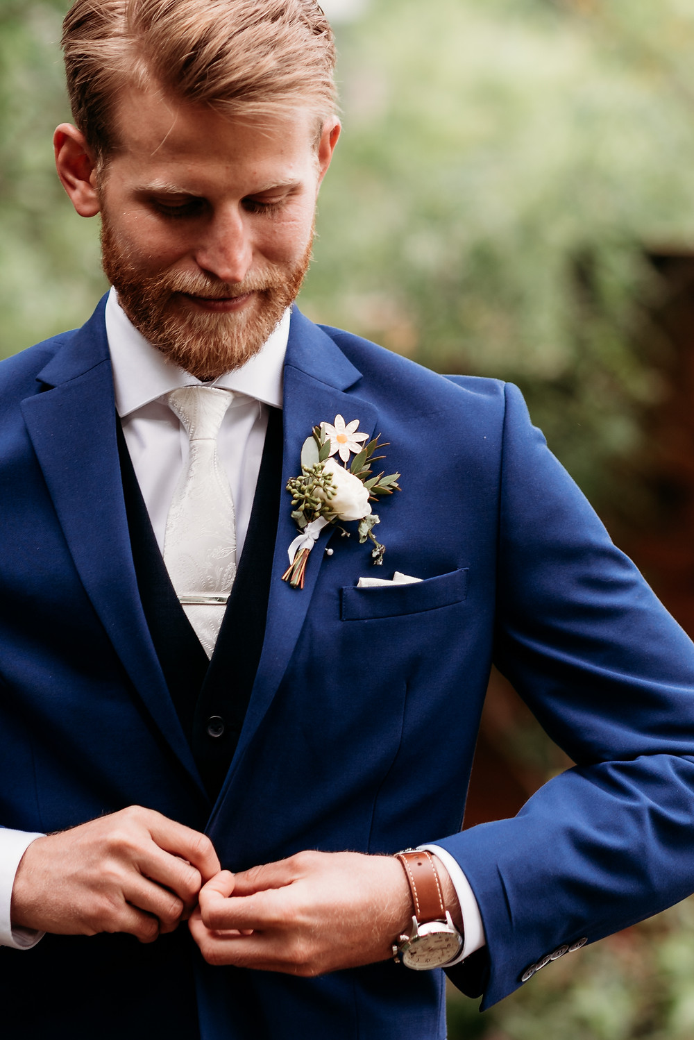 groom buttoning suit coat