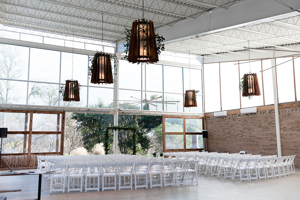 farmstead building at Barr Mansion. Open air ceremony site for weddings. chairs are facing a wall that has barn doors open in the middle which opens up to a garden. The other walls are brick and unique light fixtures hang from the ceiling
