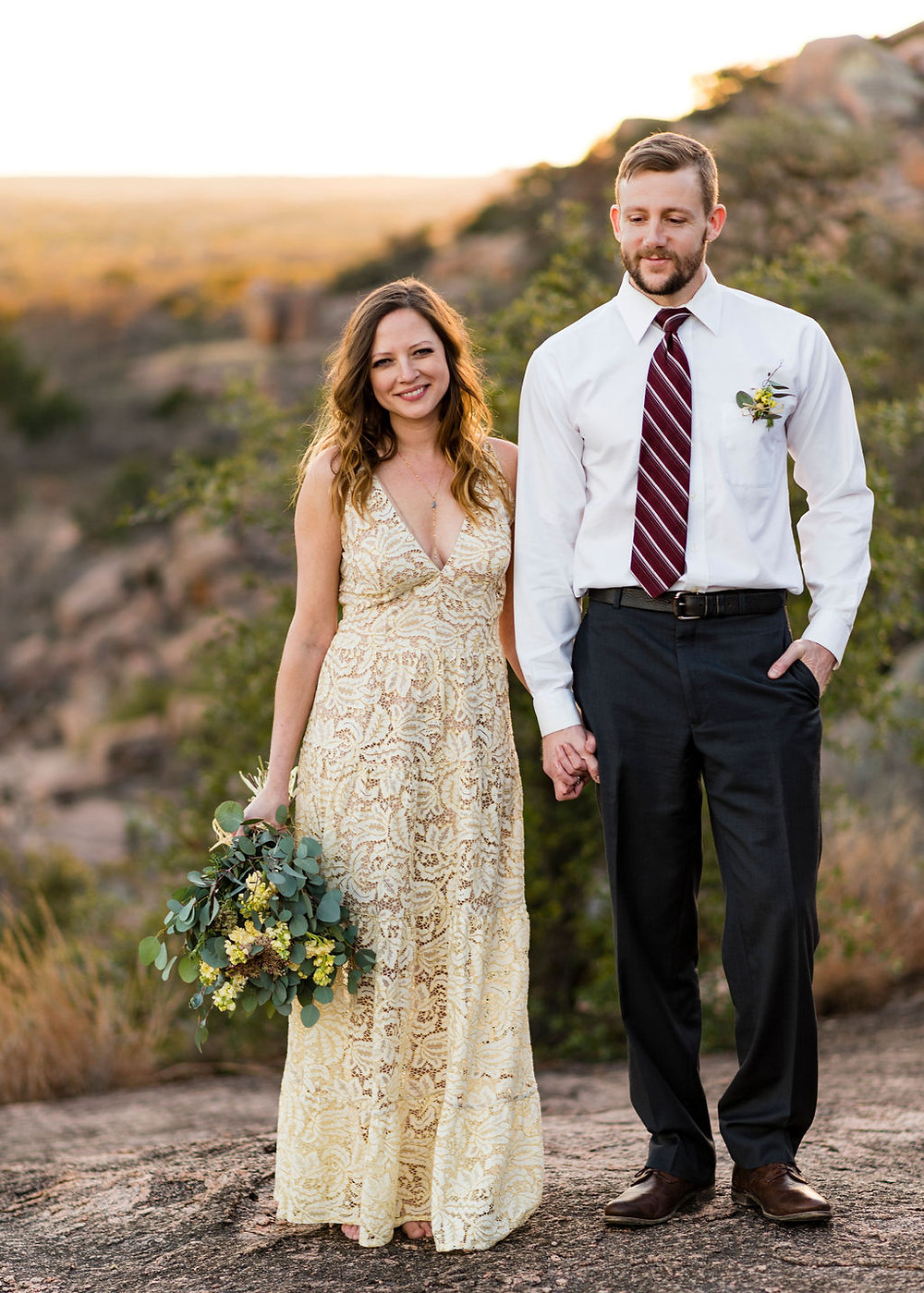 bride and groom stand side by side holding hands. bride is smiling at the camera while the groom has a shy smile looking towards the bride. They are standing on enchanted rock for their elopement with the texas hill country in the background during golden hour.