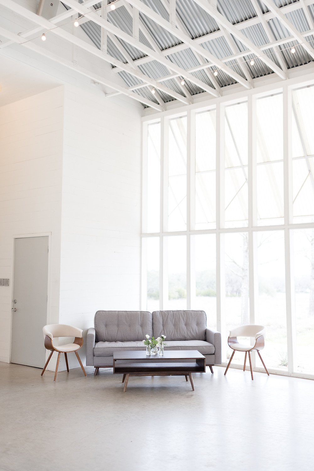 a bright, white room with tall windows, an industrial ceiling, and event rental furniture to decorate for a wedding