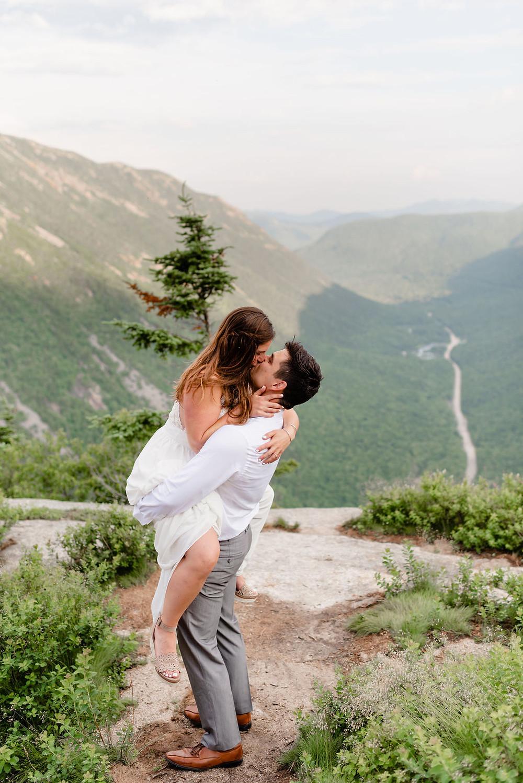 bride straddling groom in the air kissing