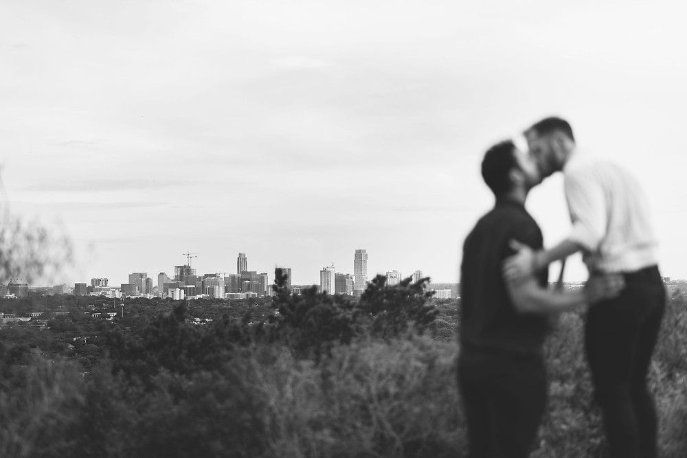 couple is out of focus in the foreground while the camera focuses on the austin skyline in the distance