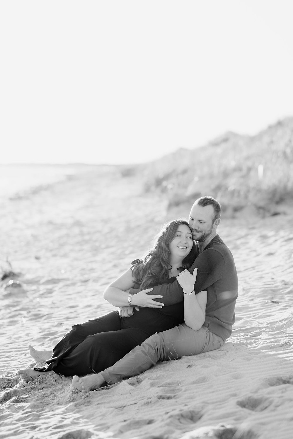 couple sitting on beach for engagement photos at lighthouse inn in West Dennis Cape cod, MA