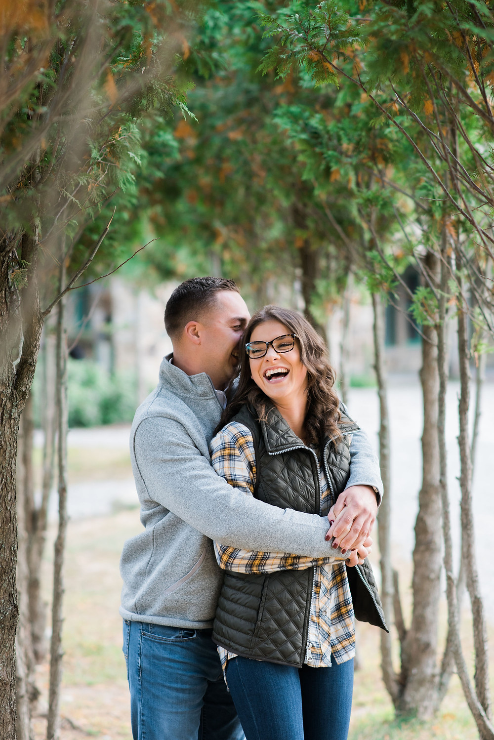 engagement photos in between trees. girl is laughing