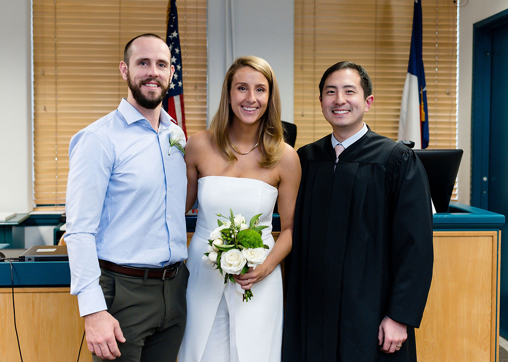 bride and groom smiling with judge chu after travis county courthouse wedding
