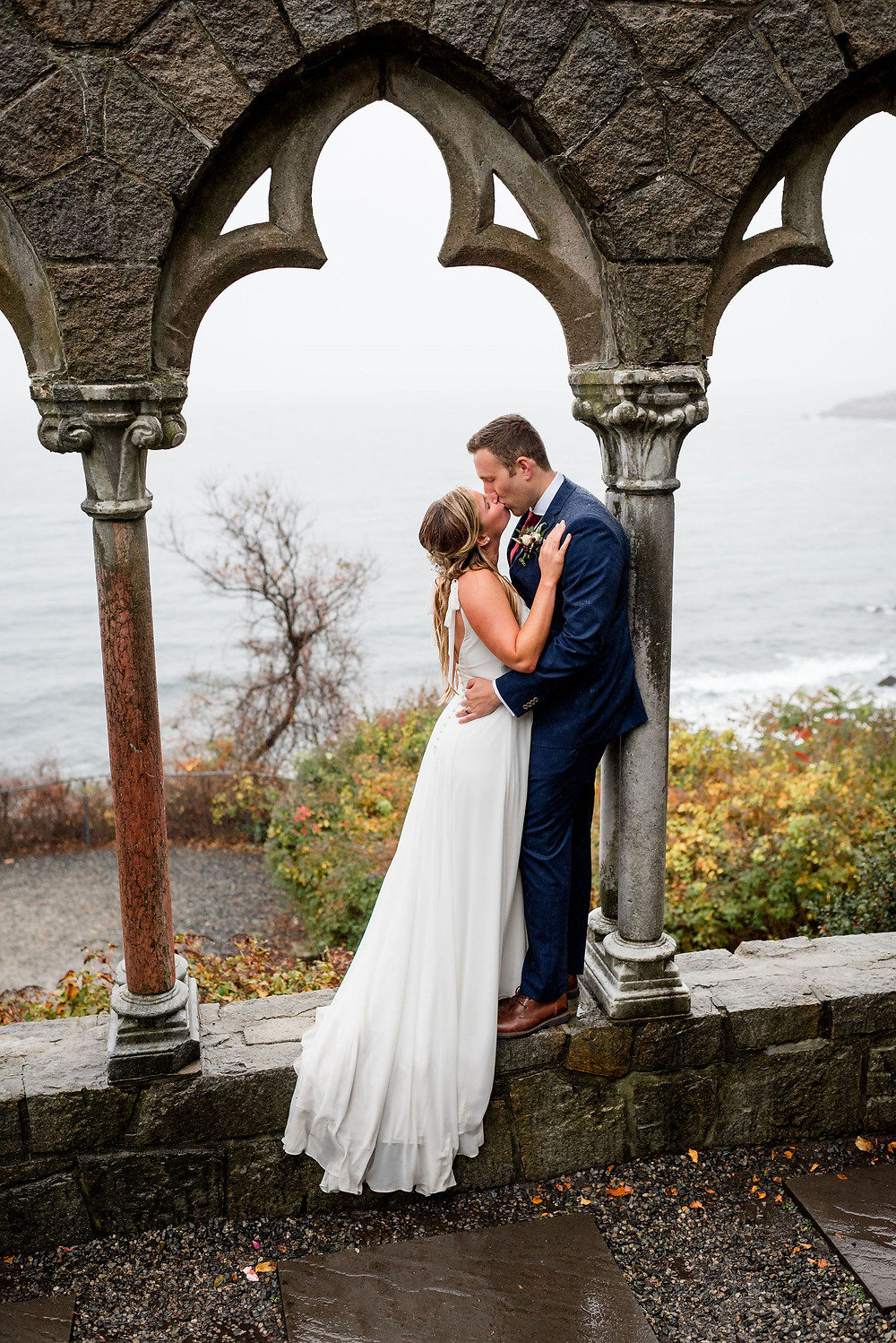 bride and groom stand in archway kissing at hammond castle