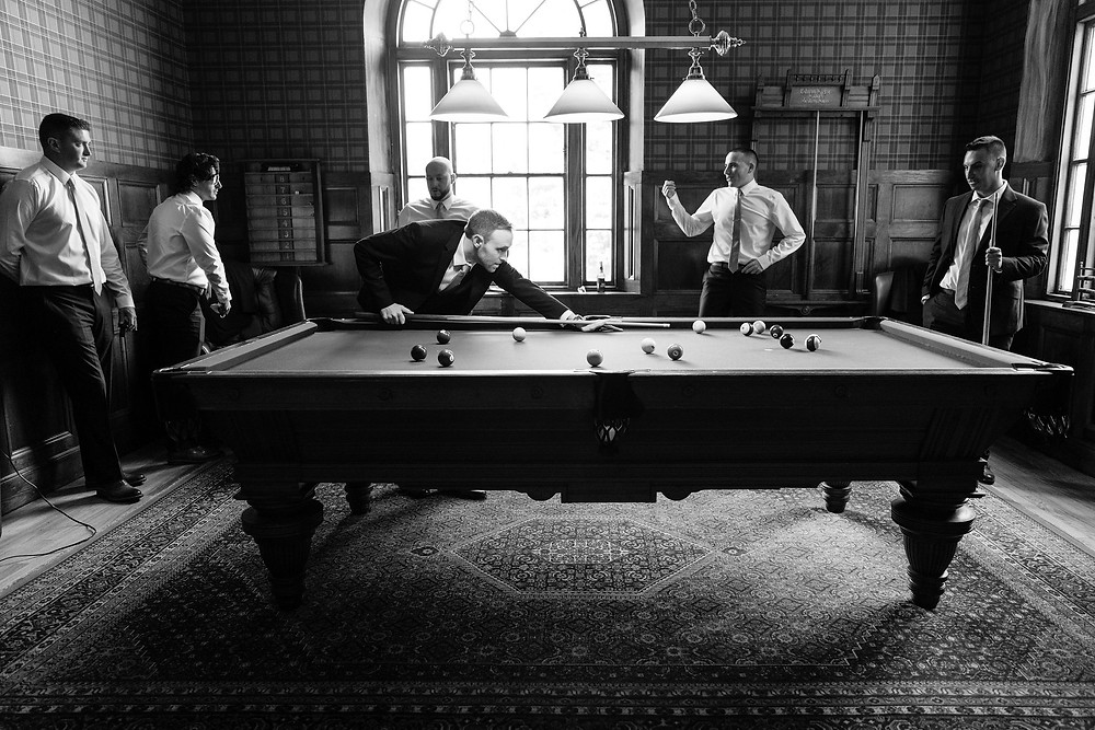 groom and groomsmen playing pool in groom's getting ready room at Tupper Manor