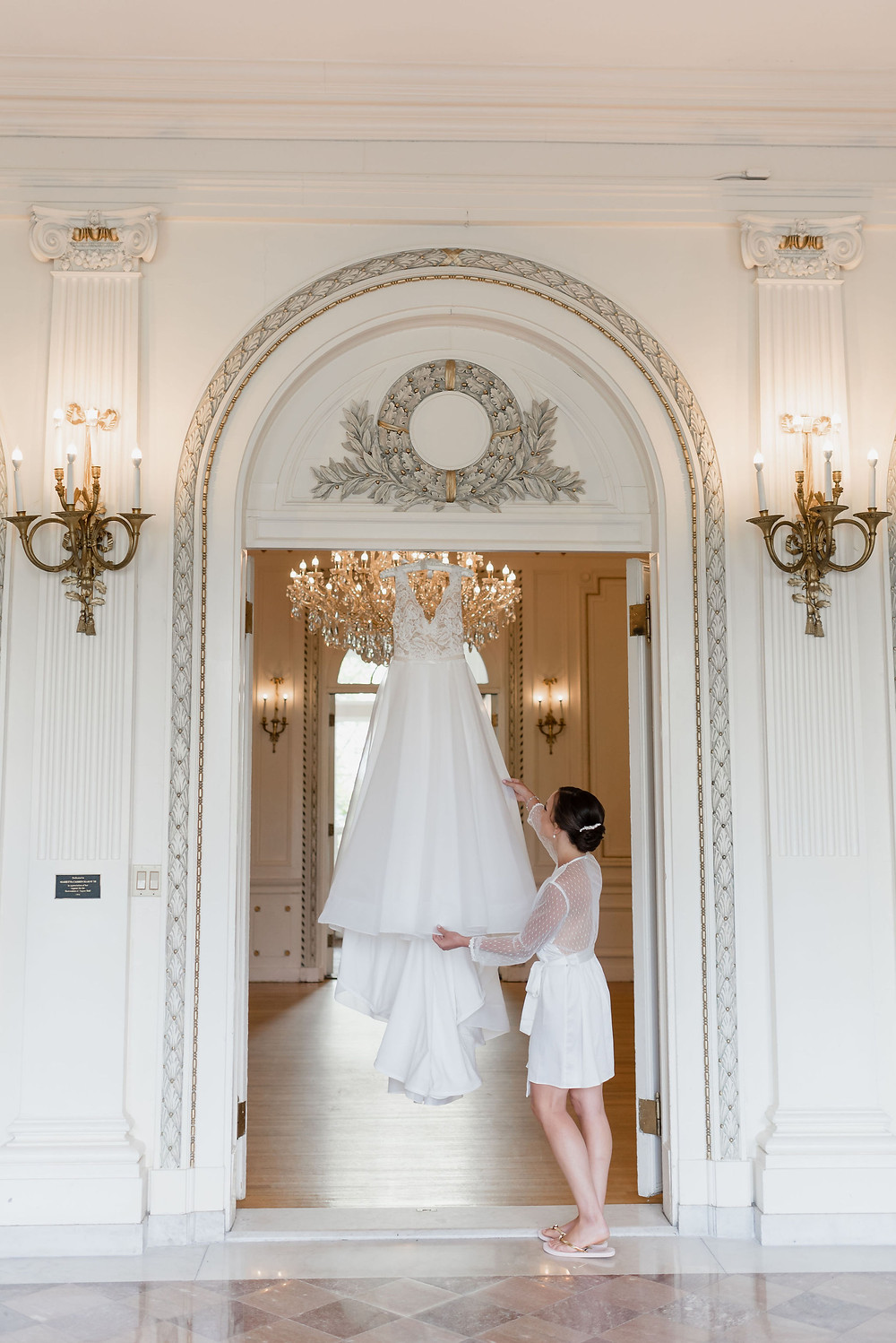 wedding dress hung up in front entryway of Tupper Manor with bride admiring it