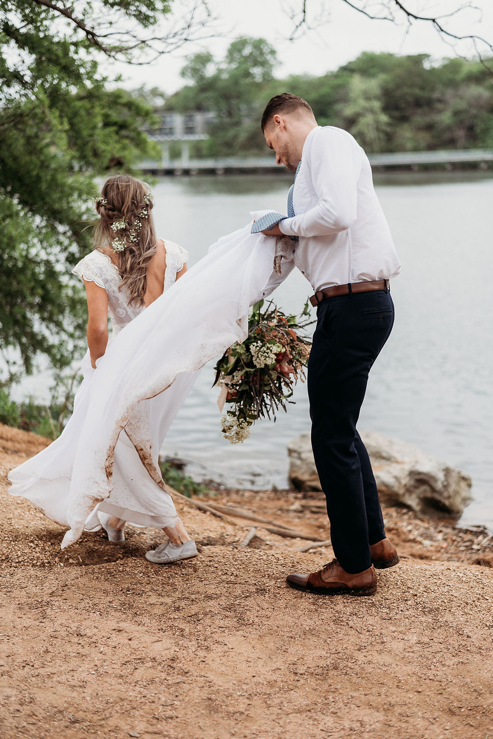 groom holds the train of brides dress as they walk. they are next to lady bird lake during their austin elopement