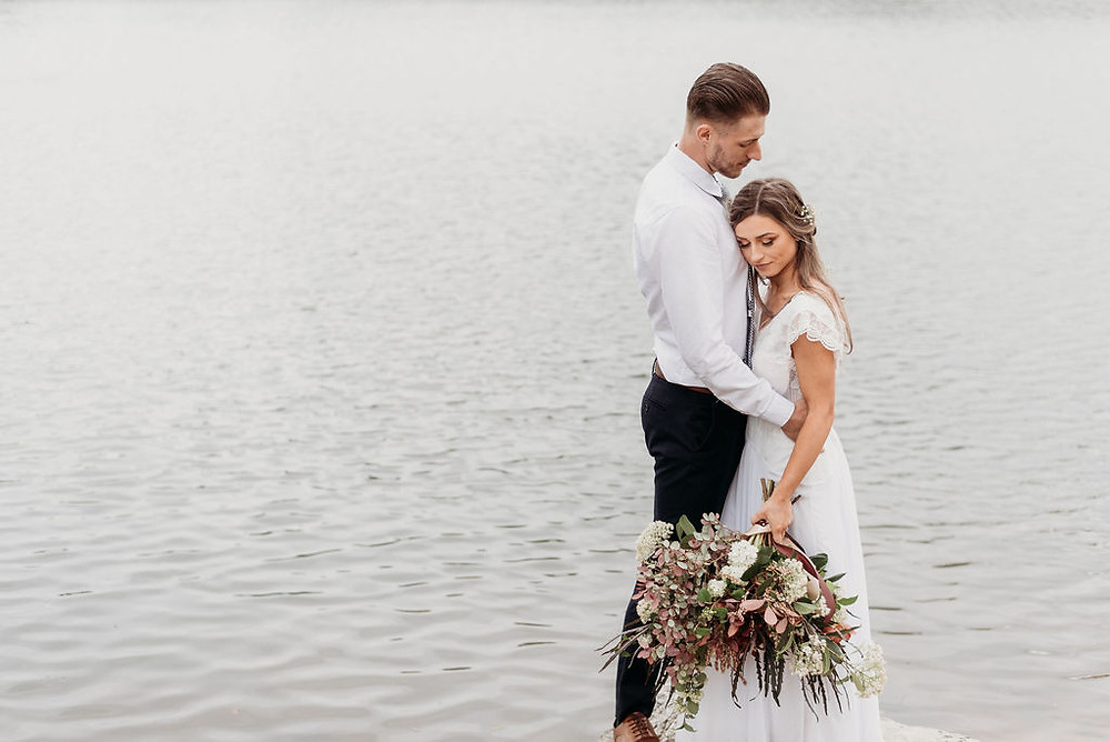 bride and groom stand on a rock in lady bird lake during their austin elopement for their newly wed portraits. bride and groom stand chest to chest with the bride's face buried in the grooms chest. his arms are around her and she holds the bouquet down to her side