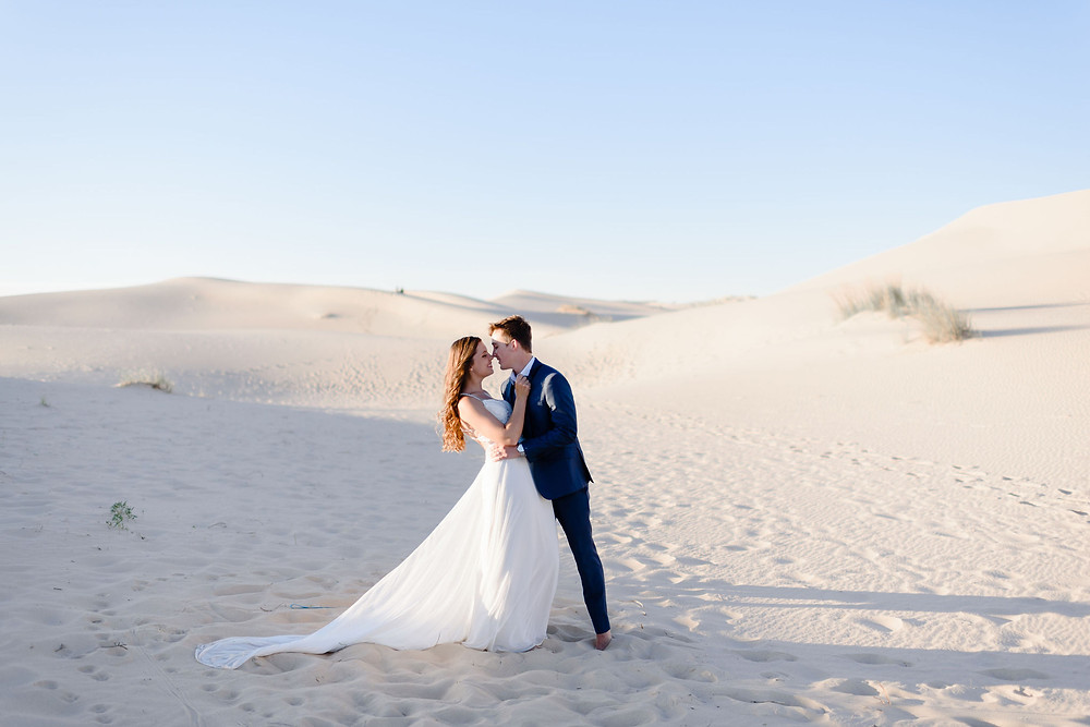 couple is chest to chest and about to kiss. you can see the view of monahans sandhills in the distance