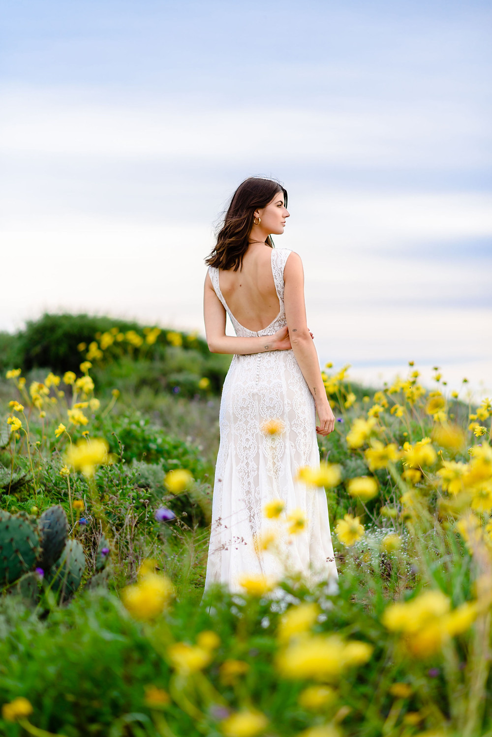 bride posing in field of yellow wild flowers