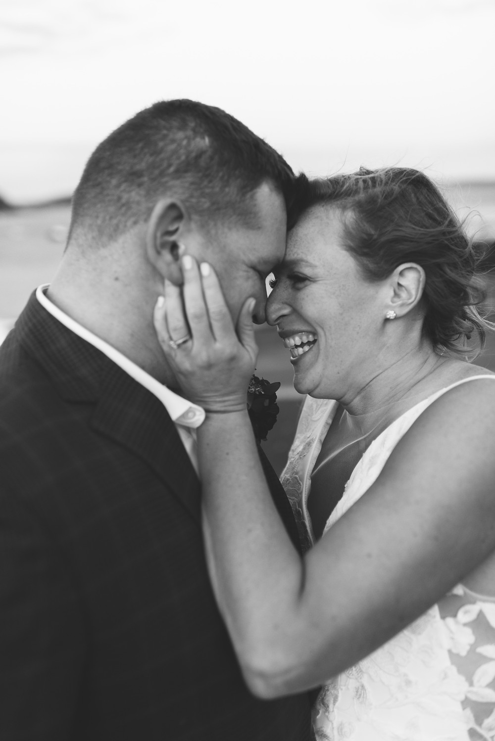 black and white photo close up of couple forehead to forehead with bride pulling groom's face in