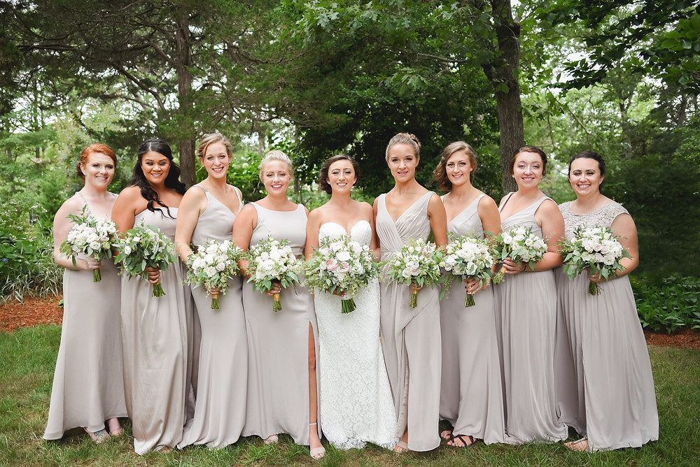 bridesmaids in a line smiling with bouquets