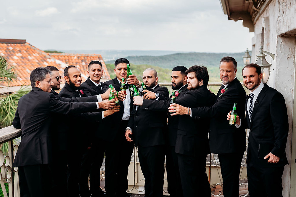 groomsmen cheers beer on the balcony of villa antonia grooms suite