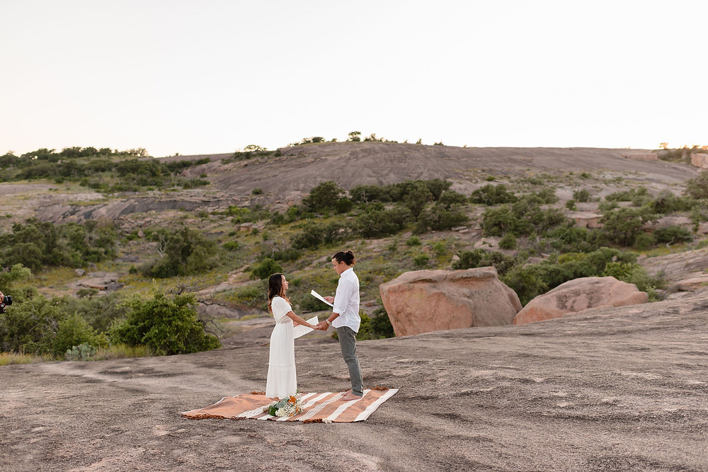 bride and groom holding hands during their elopement at enchanted rock. they are small in the frame and you can see a lot of the rocky scenery