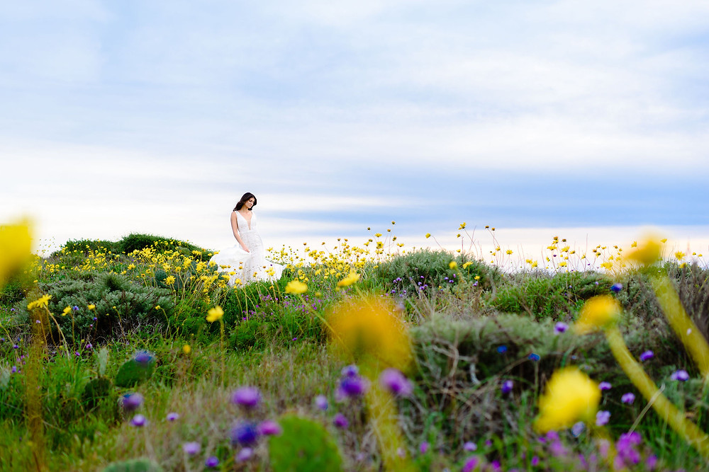 bride in a field of yellow and purple wildflowers