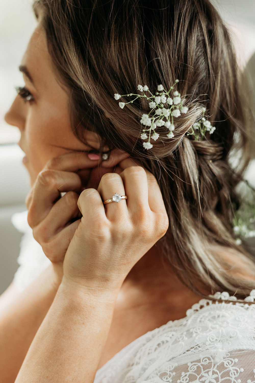 bride is putting on earrings. you can see her engagement ring and her hair style during their Austin elopement