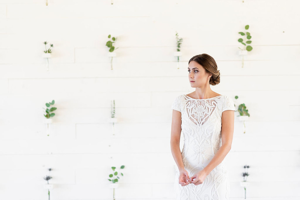 bride nervously picking at her fingers before the wedding. standing in front of white wall with plants
