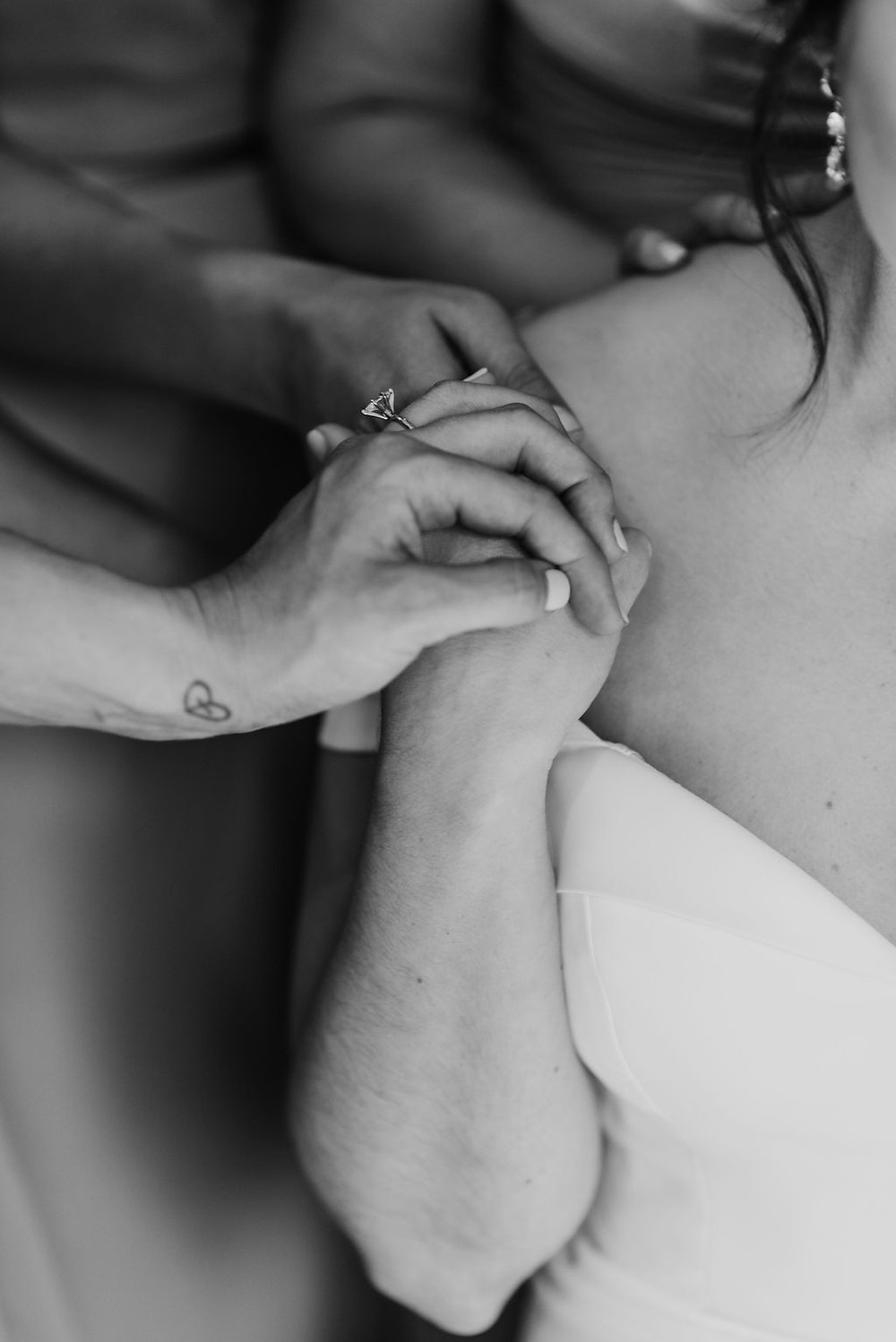 close up of hands on bride's shoulder while bridesmaids pray over bride at villa antonia