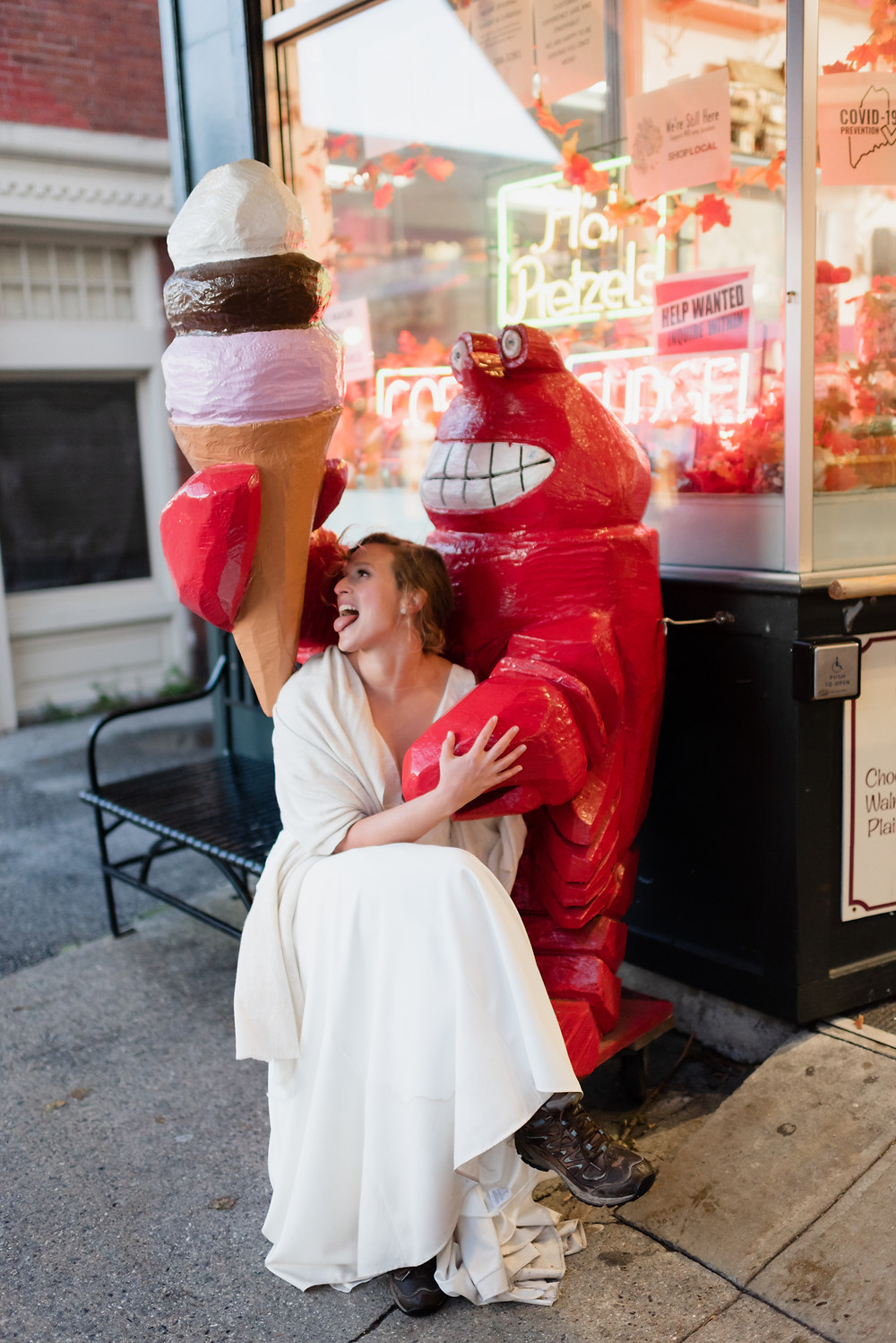 bride sitting on lobster holding ice cream cone outside of Ben & Bill's Chocolate Emporium in Bar Harbor, Maine