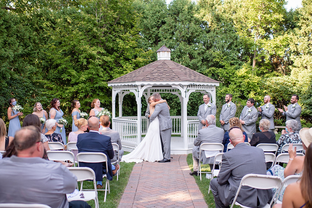 first kiss as husband and wife during wedding at chocksett inn in front of the gazebo