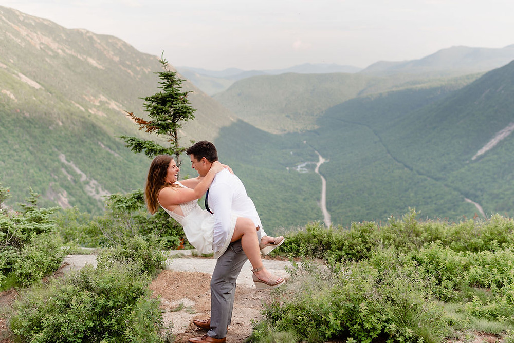 bride and groom being silly on mountain with great view of new Hampshire in the background