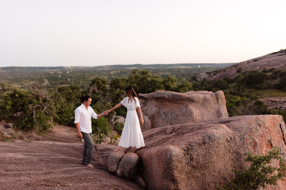 groom helps bride off of large rock at enchanted rock