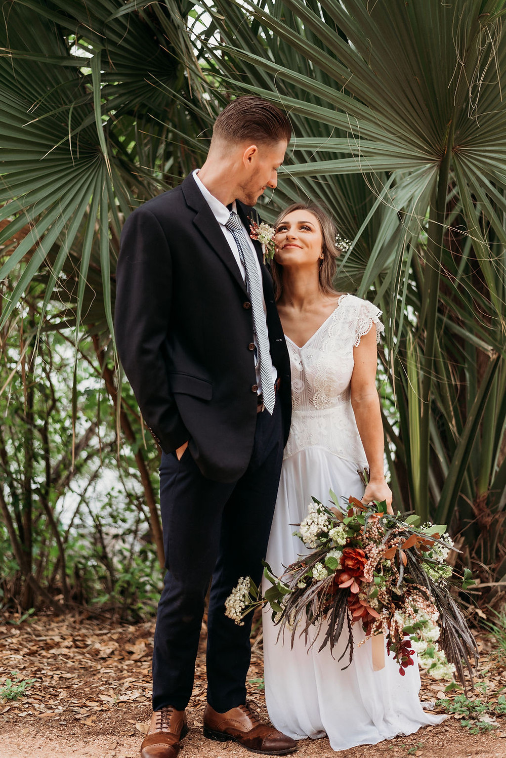 bride and groom are posed in front of palm trees by lady bird lake during their austin elopement