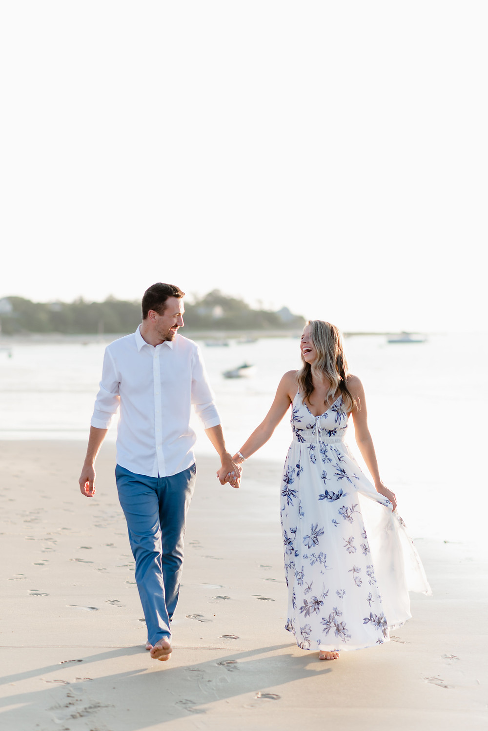 couple walking hand in hand on the beach for engagement photos during golden hour
