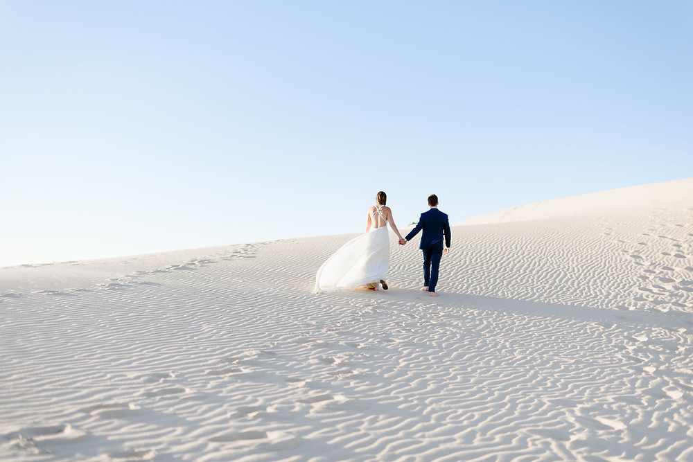 couple walks away from camera holding hands up one of the sand hills. The sand has an intricate pattern from the wind and they are walking through an undisturbed patch of sand