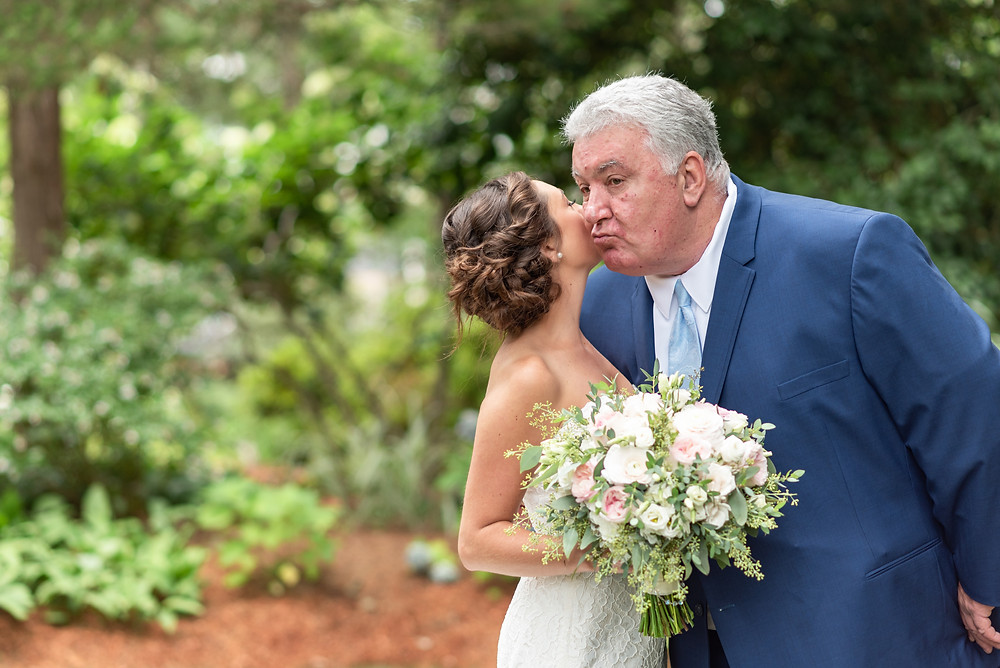 bride and father kissing on cheek
