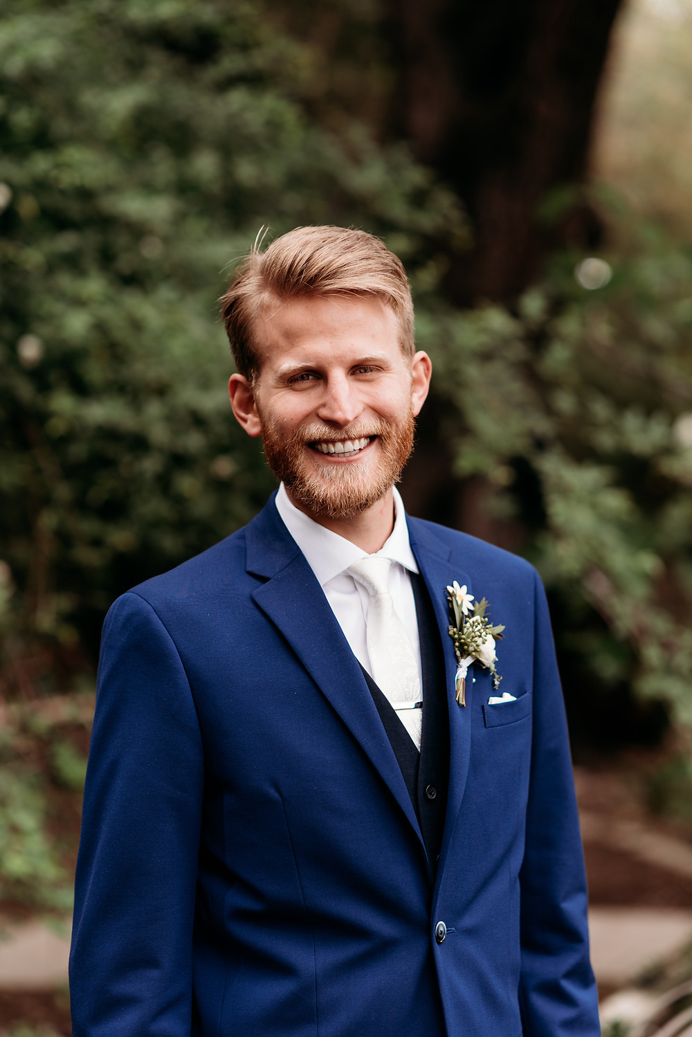 groom looking at camera in a navy suit and white tie
