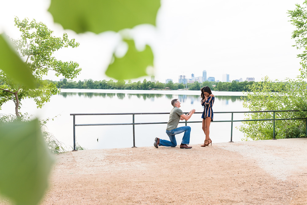 man down on one knee during proposal on the east side of lady bird lake in austin texas