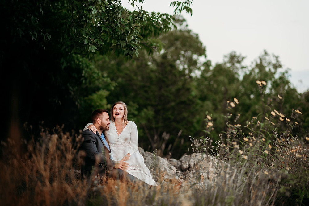 couple sits on the ground together with plants in the foreground. the bride is laughing