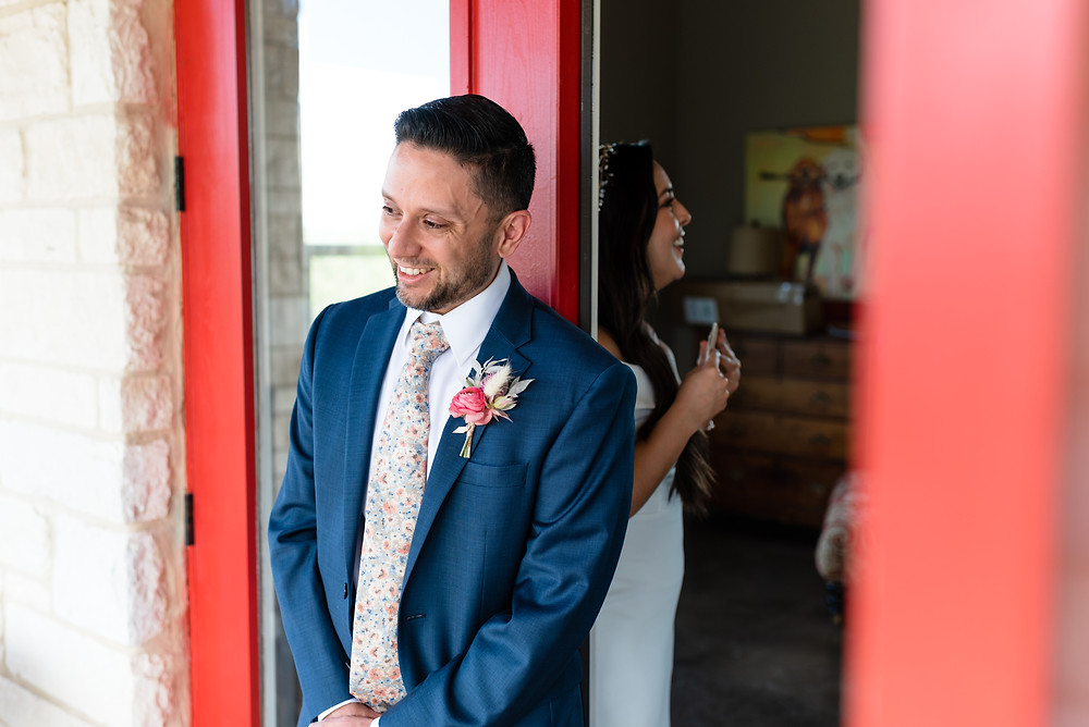bride and groom stand on each side of a closed door holding hands for their no look first look before their wedding. you can see the groom mostly and he is smiling really big