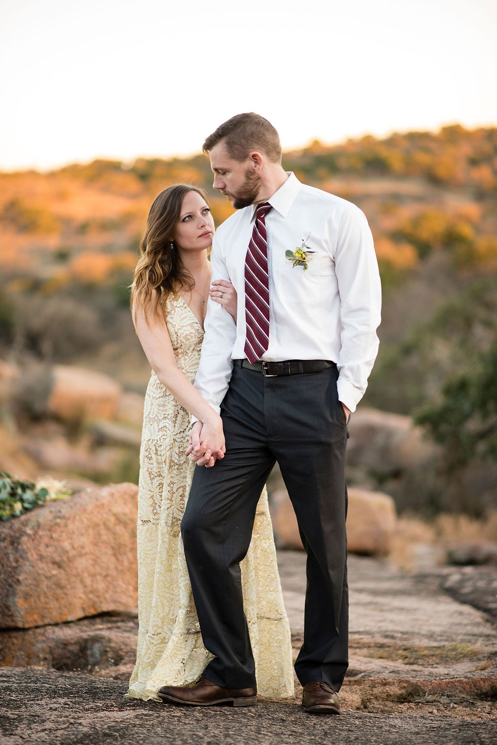 newlyweds pose for photo during enchanted rock elopement. Groom is standing slightly in front of bride with one foot raised. The bride is holding his hand with one arm and the other is wrapped around the groom's bicep. They look at each other seriously