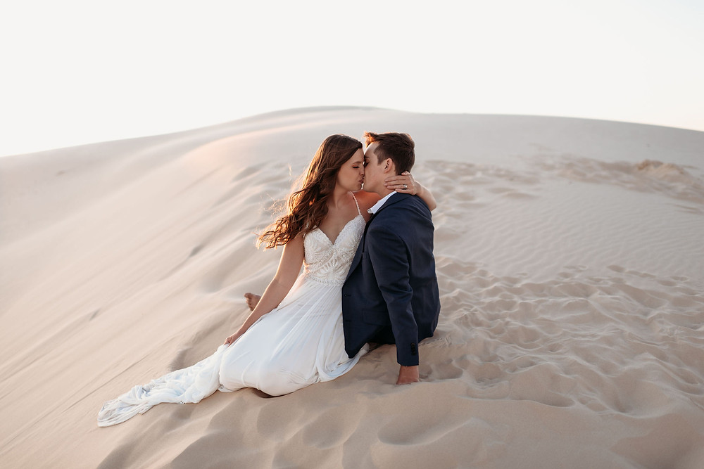 the couple sits together in the sand. the bride has her hand wrapped around the grooms neck, embracing him. the groom is leaning on his hand in the sand.