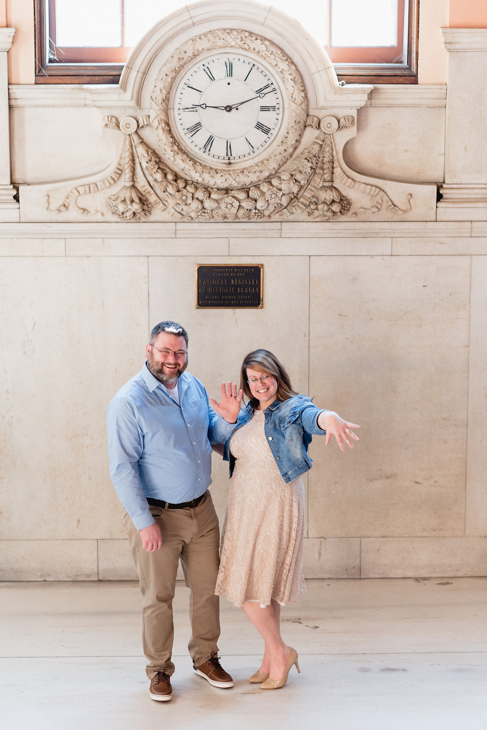 couple showing off their new wedding rings for the camera in front of grand clock