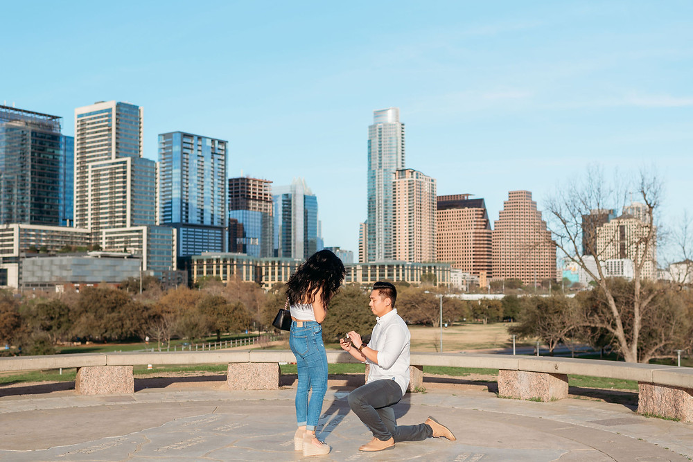 doug sahm hill downtown austin proposal. guy down on one knee asking his girlfriend to marry him with the austin skyline in the backgorund