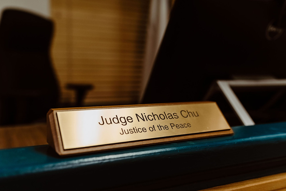 Judge Nicholas Chu Justice of the Peace name plate on desk of courtoom at travis county courthouse